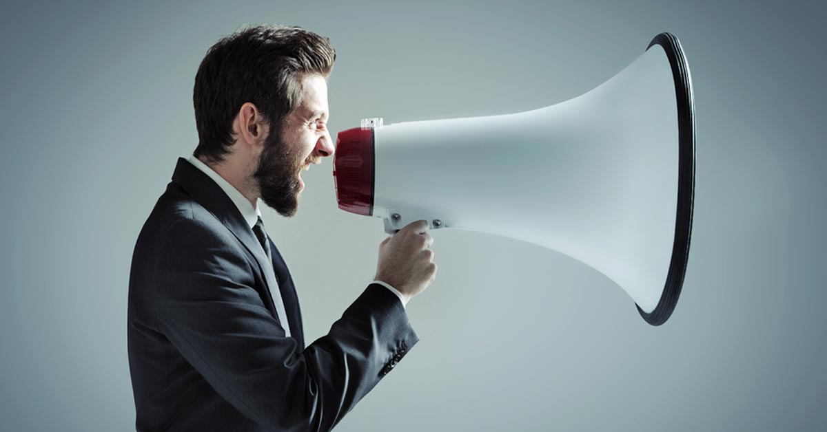 Man in suit yelling into giant megaphone